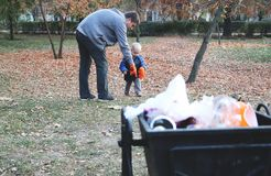 Padre y poco barrido del hijo en el parque Fondo - basura y cubo de la basura El concepto de ecología y de proteger el planeta fotos de archivo libres de regalías