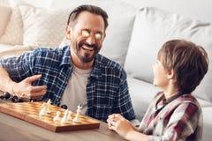 Padre y poco hijo en casa que se sientan en el papá de la tabla que lleva a cabo pedazos de ajedrez en los ojos que miran al much imagenes de archivo