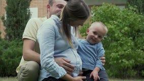 Padre y poco hijo que abrazan a la mamá embarazada metrajes