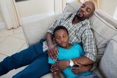 Padre y relajación en el sofá en sala de estar Imágenes de archivo libres de regalías