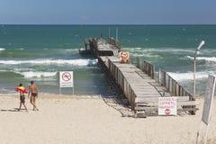 Padre y sol que caminan en la playa cerca del embarcadero Foto de archivo libre de regalías
