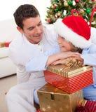 Padre y su hijo que desempaquetan los regalos de la Navidad Fotografía de archivo libre de regalías