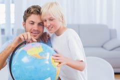 Padre y su muchacho que miran el globo Foto de archivo