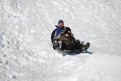 Padre y su sledding de dos hijos foto de archivo