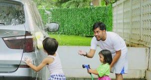 Padre y sus niños que lavan el coche almacen de metraje de vídeo