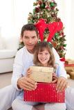Padre y sus regalos de la Navidad de la apertura de la hija Foto de archivo