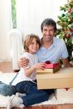 Padre y sus regalos de la Navidad de la apertura del hijo Imagen de archivo libre de regalías