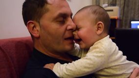Padre y sus seis meses lindos del bebé que abraza y que habla, pasando una cierta hora de la calidad junta metrajes