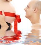 Padre y vientre orgullosos con la cinta roja en agua Imagenes de archivo