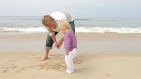 Padre And Young Daughter alle immagini del disegno della spiaggia in sabbia stock footage