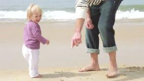 Padre And Young Daughter che raccoglie le conchiglie su Shoreline stock footage