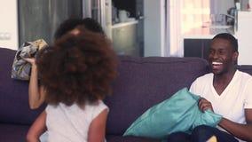 Padres africanos felices de la familia con la hija del niño que tiene lucha de almohada almacen de video