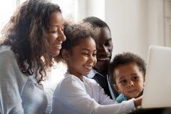 Padres africanos y niños que ríen haciendo compras en línea en l imagen de archivo