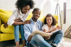 padres afroamericanos felices y pequeño libro de lectura de la hija junto fotos de archivo
