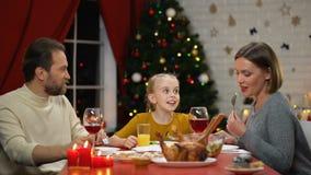 Padres alegres e hija que comen la ensalada fresca el la víspera de Navidad, día de fiesta junta almacen de metraje de vídeo