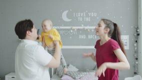 Padres alegres que bailan con la niña pequeña en dormitorio metrajes