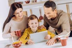 Padres alegres que miran un vídeo así como su hijo Imagenes de archivo