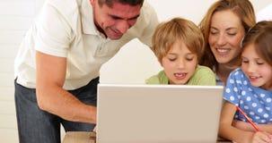 Padres alegres y niños que hacen artes y artes así como el ordenador portátil almacen de metraje de vídeo