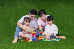 Padres asiáticos e hijas chinos que juegan bloques en la hierba Foto de archivo
