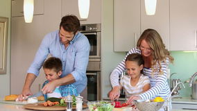 Padres atentos y sus niños que cocinan junto almacen de metraje de vídeo