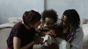 Padres cariñosos de la raza mixta que besan al pequeño hijo almacen de video