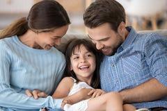 Padres cariñosos felices que cosquillean a la hija del niño que se divierte que ríe t foto de archivo