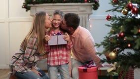 Padres cariñosos que besan a la hija el Nochebuena almacen de metraje de vídeo