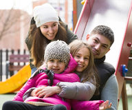 Padres con dos hijas que juegan en el children& x27; diapositiva de s Fotos de archivo