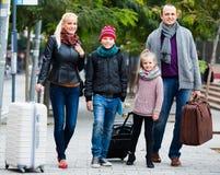 Padres con dos niños que persiguen las calles Fotografía de archivo
