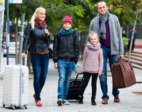 Padres con dos niños que persiguen las calles Fotos de archivo libres de regalías