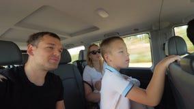 Padres con dos niños que tienen viaje del coche almacen de video
