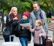 Padres con dos niños y equipaje con el mapa Foto de archivo
