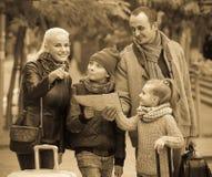 Padres con dos niños y equipaje con el mapa Imagenes de archivo