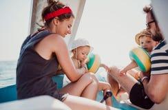 Padres con dos peque?os ni?os del ni?o que se sientan en el barco el vacaciones de verano imagen de archivo