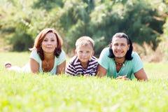 Padres con el adolescente en hierba en el parque Imágenes de archivo libres de regalías
