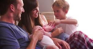 Padres con el bebé de alimentación del hijo en cama con la botella