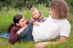 Padres con el bebé en mentiras de la naturaleza imágenes de archivo libres de regalías