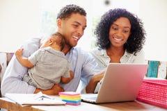 Padres con el bebé que trabaja en oficina en casa Imagenes de archivo