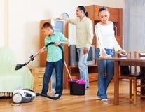 Padres con el hijo adolescente que hace la limpieza de la casa Imagenes de archivo
