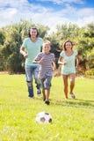 Padres con el hijo adolescente que juega con la bola Fotografía de archivo libre de regalías