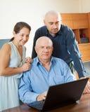 Padres con el hijo adulto en Internet Imagen de archivo