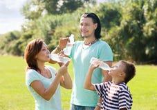 Padres con el hijo del adolescente que bebe la agua fría Imagen de archivo