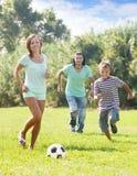 Padres con el hijo del adolescente que juega con el balón de fútbol Foto de archivo