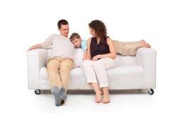 Padres con el hijo en el sofá del cuero blanco Imágenes de archivo libres de regalías