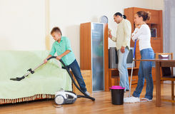 Padres con el hijo que hace la limpieza de la casa en hogar Fotos de archivo libres de regalías