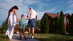 Padres con el niño, el retrato de una familia feliz, la madre y el padre que llevan a cabo las manos hijo, muchacho que tiene ris almacen de video