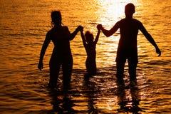 Padres con el niño en el mar en puesta del sol Imagen de archivo libre de regalías