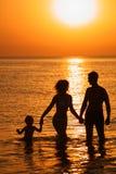 Padres con el niño en el mar en puesta del sol Foto de archivo