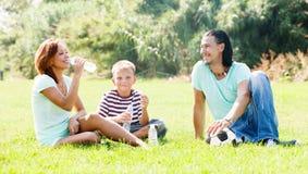 Padres con el niño que bebe de las botellas Imagenes de archivo