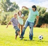 Padres con el niño que juega con el balón de fútbol Imagenes de archivo